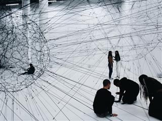 people working on a large-scale sculpture made of strings