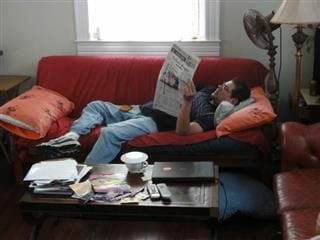 Man laying on a couch reading a newspaper.