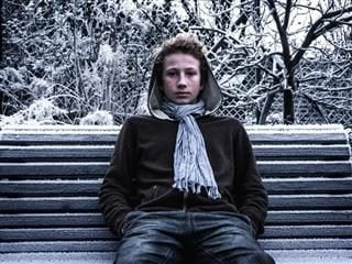 man sitting on a park bench in winter
