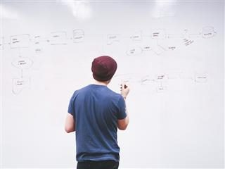 man writing on a whiteboard