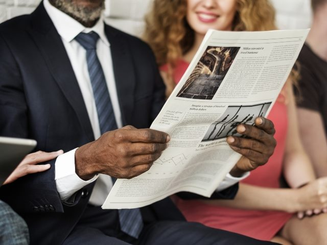 Man and woman reading a newspaper. The man is holding the newspaper.