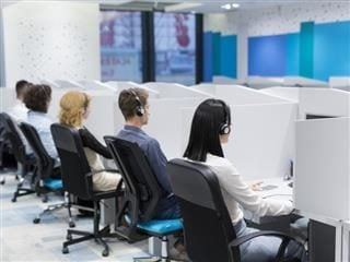 Group of young business people with headset working and giving support to customers in a call center office.