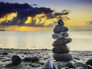 Rocks aligned on a beach with and ocean and a beautiful sunset happening in the background