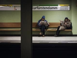 two men reading newspapers in the Berlin UBahn