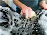 A person scrubbing a laptop inside a sink with soap and water. Data Hygiene Concept