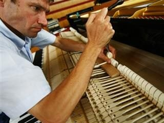 man in process of tuning a piano