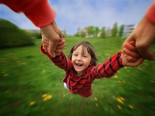 wide angle shot of laughing child being held by hands and spun in circles