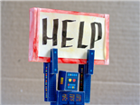 A cardboard robot holding a sign over its head that reads help