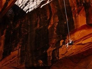 person hanging on a rope, descending into a cave