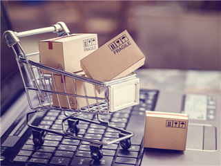 Shipping boxes loaded into a shopping cart on top of a laptop keyboard - ecommerce concept