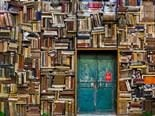 aqua colored door surrounded by haphazard stacks of books