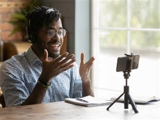 young man sitting at a table recording a video using his mobile phone