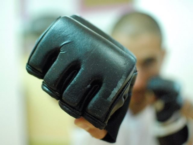 close up of a boxing glove with person behind it