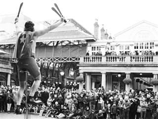 man on unicycle wearing a cape juggling swords in front of a crowd