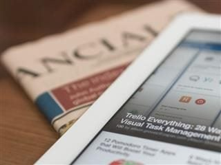 A newspaper and a tablet with a news website open - newsbyte concept