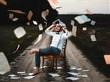 man protecting his head from paper flying around with a book