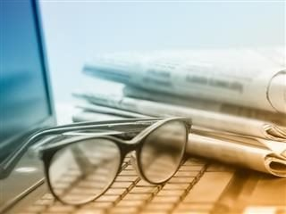 A pair of glasses resting on top of a laptop computer near a newspaper.