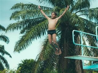 boy jumping off a diving board with hands in the air giving the peace symbol