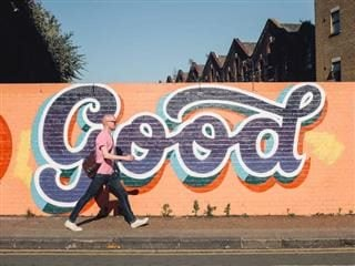 "walking in front of graffiti that says ""good"""