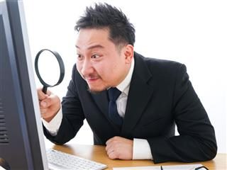 A businessman peering through a magnifying glass at his PC's monitor. CDP Evaluation Concept