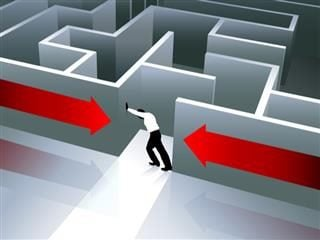 An office worker pushing away the walls of a maze.