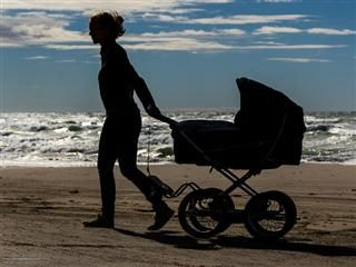 the lonely stroll of a woman and her baby on the beach