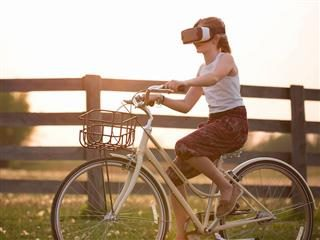 woman riding a bicycle with VR goggles on