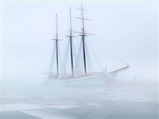 ship navigating ice floes in the fog