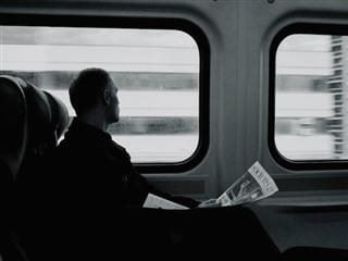 man on train with a newspaper