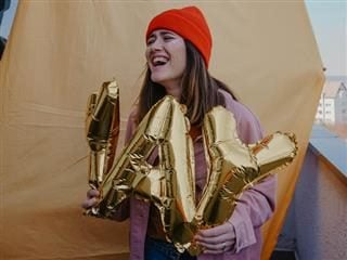 """woman holding balloons that spell out """"YAY"""""""