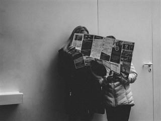 two people sharing a newspaper