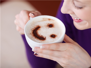 A happy customer drinking coffee with a smiley face etched in the creamy top