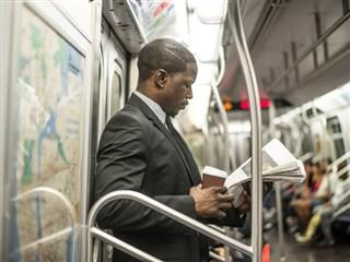 Man in business suit standing up reading a newspaper with coffee in hand.