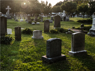 Social Media Marketing concept - A cemetery with many tombstones and trees, set against a setting sun