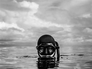 scuba diver breaking  the surface of the water