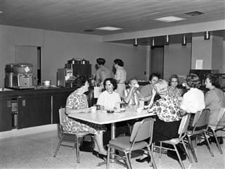 Black-and-white photo of women sitting at a lunch table during a break from work in the 1960s.