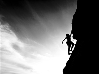 A climber is silhouetted against the evening sky as she clings to a steep rock face