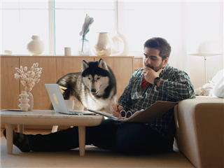 A man working from home, having a video call, with his dog sitting near him.