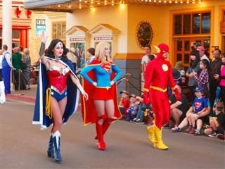 wonder woman, super girl and flash walking down a street
