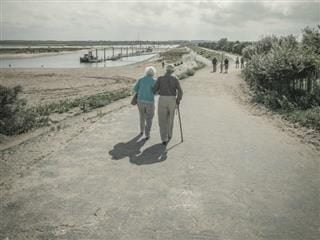 older couple walking with a cane