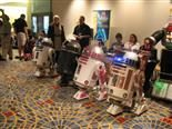 A row of four R2D2s robot models from the movie Star Wars in a movie theater lobby surrounded by people.