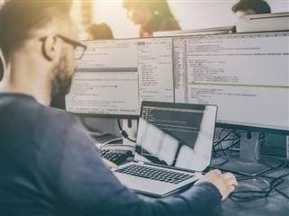 Homme assis et travaillant sur plusieurs terminaux informatiques.