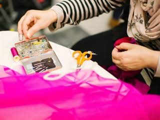 seamstress working on a hot pink garment