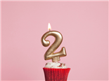 A birthday cupcake with a number 2-shaped lit candle.