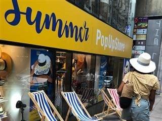 woman walking past a summer pop up shop