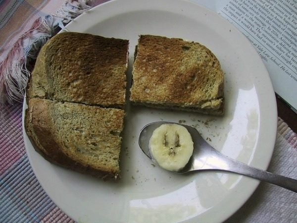 three pieces of toast and a banana slice on a spoon