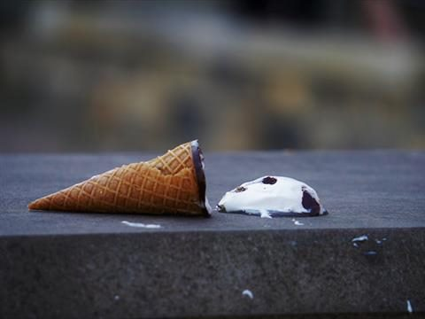 dropped ice cream cone melting  on the sidewalk