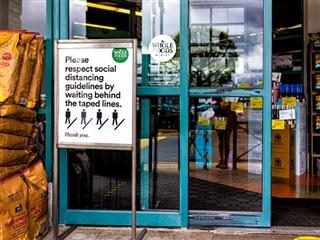 A storefront with a sign outside on social distancing guidelines. - brick and mortar concept