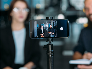Business woman and man shooting video using smartphone on tripod - video marketing concept