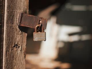 broken rusty old lock leaving a door open